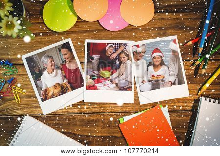 Snow falling against overhead view of office supplies with blank instant photos
