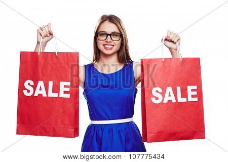 Elegant shopper in blue dress holding two sale paperbags