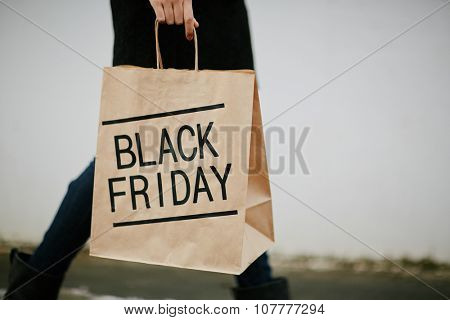 Young woman in black carrying paperbag on Black Friday