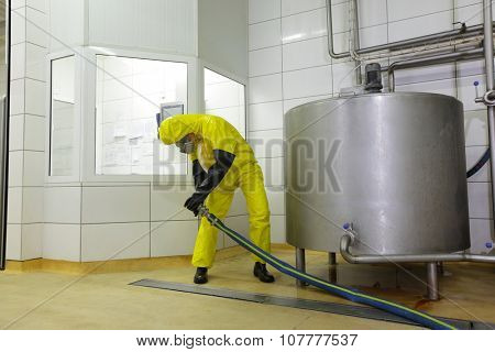 technician in protective coveralls with large hose at industrial tank in plant
