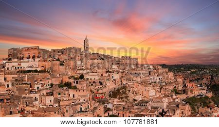 Panoramic View Of Typical Stones And Church Of Matera Under Sunset Sky