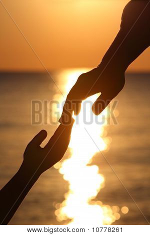 Silhouettes Of Two Hands Child And Mother Adjoin Fingers