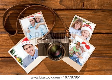 Cute couple in santa hats shopping online with laptop against instant photos on wooden floor