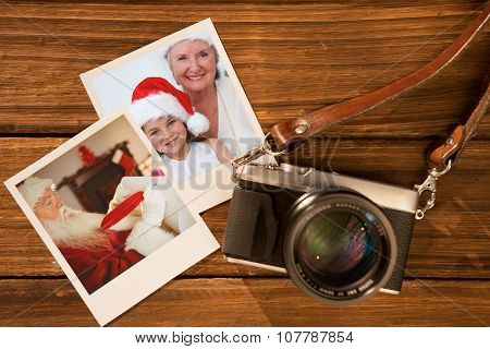 Smiling grandmother and little girl baking Christmas cakes against instant photos on wooden floor