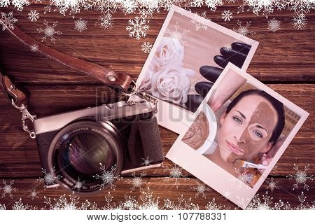 Peaceful brunette getting a mud facial applied against close up roses and a black pebbles stack