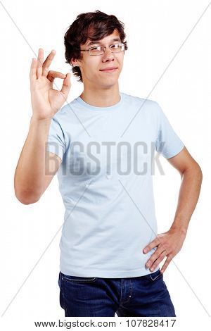 Young hispanic man wearing glasses, blue t-shirt and jeans showing A-ok hand gesture with discreet smile isolated on white background - success concept