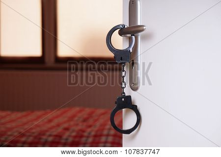 handcuffs are hanging from bedroom door handle poster