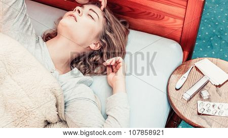 Sick woman suffering from headache pain. Ill girl laying in bed caught cold. Thermometer and pills on table. poster