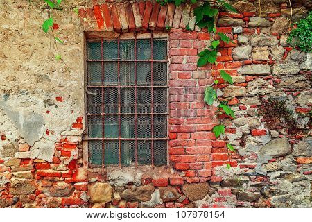 Fragment of old abandoned brick house with closed window behind iron bars in small italian town in Piedmont, Northern Italy.