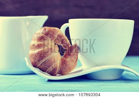 closeup of a cup of coffee or tea and a croissant, on a blue wooden table set with a ceramic milk pot