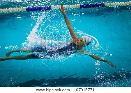 young beautiful girl swims backstroke
