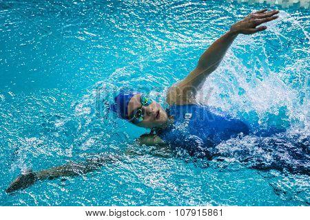 girl athlete swims backstroke, around her spray of water
