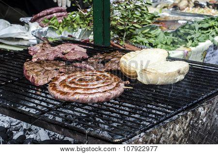 Typical Sardinian Food. Sausages Roast, Bread, Steaks Roast In A Typical Sardinian Community Festiva