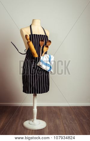 Kitchen apron with baking utensils in the pocket with vintage tone poster