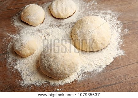 Dough balls for pizza on floured wooden board poster