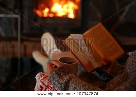 Woman resting with cup of hot drink and book near fireplace