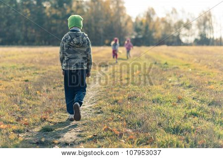 Sad boy walking slowly in a distance behind laughing children ** Note: Soft Focus at 100%, best at smaller sizes