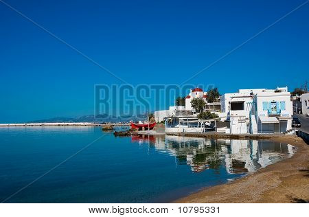 The Famous Tavern On The Sea Shore Of The Bay Of The Island Of Mykonos With A Red Boat And The Churc