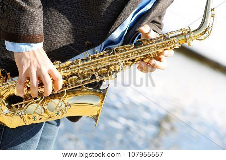 Saxophonist plays jazz outdoors, close up