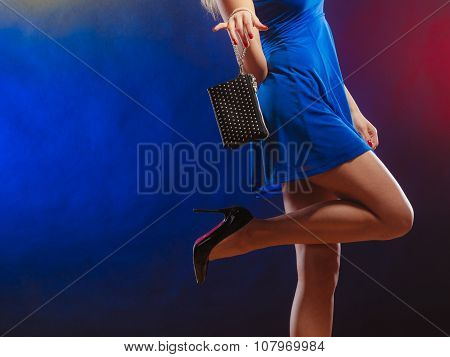 Celebration disco and evening fashion concept - woman in blue dress holding handbag bag dancing in the club part of body female legs in high heels on party floor poster