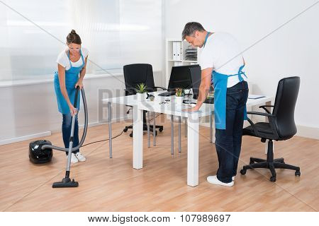 Two Janitors Are Cleaning The Office