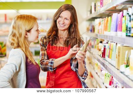 Woman in drugstore gets advice from saleswoman while shopping for cosmetics