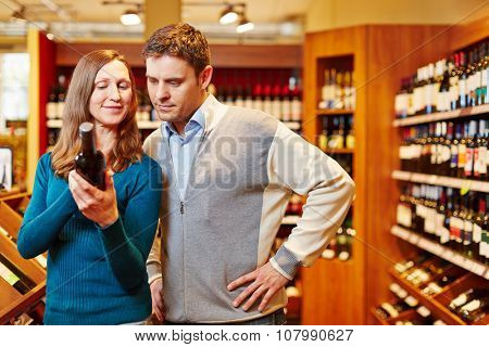 Couple shopping for bottle of red wine in a beverage market