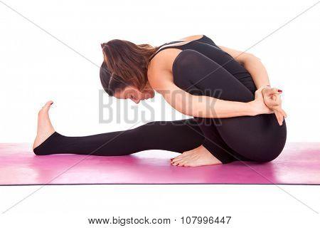 Beautiful woman doing Marichyasana pose on yoga class. Studio shot.