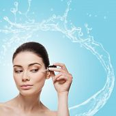 Beautiful young woman applying anti-ageing moisturizing serum to under eye area. Isolated over light blue background with water splash. Square composition. Copy space. poster