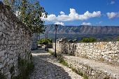 stone walls of old fortress and mountains in background, Berat, Albania poster