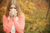 Sick woman in fall autumn park sneezing in tissue. Ill girl caught cold flu outdoor. Rhinitis or allergy. Health care. poster