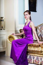 Woman In Purple Dress In Luxury Interior.