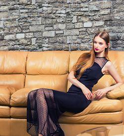 Beautiful Woman In Classic Black Dress In Luxury Interior.