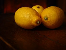 Rustic lemons on a dark wooden table in natural soft light