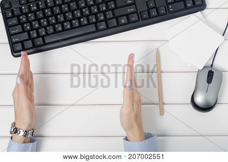 Female hands showing notes for keyboard mouse from computer on white wooden background isolation