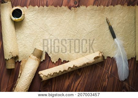 White Feather And Ancient Scroll On Brown Plank