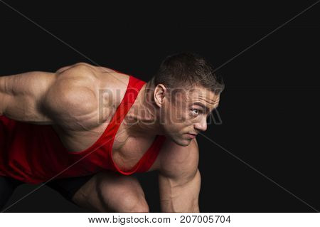Strong Bodybuilder Man Ready to Start on Black Background