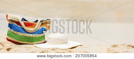 Straw hat and bag on a tropical beach with white sand on exotic Caribbean island