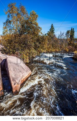 Foam water rapids on the smooth stones of the Winnipeg River. The concept of ecological and adventure tourism Warm clear autumn day
