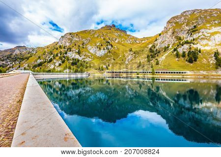Mountain Lake Lago di Fedaia, Dolomites. Glacial lake with clear cold water. Powerful dam blocked the lake. The concept of ecological and extreme tourism
