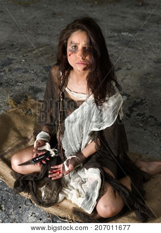 Scared young woman in rags sitting in derelict building wounded, abused and bleeding