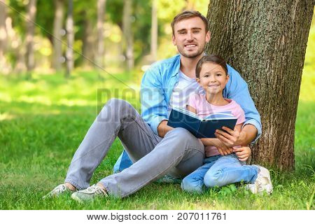 Young man and his little daughter reading book in park