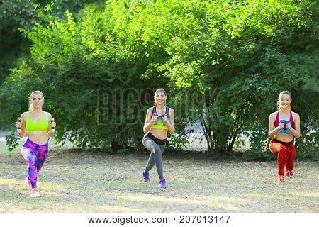 Young sporty women with dumb-bells doing exercise outdoor