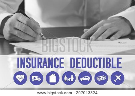 Man signing document at table. Concept of insurance deductible