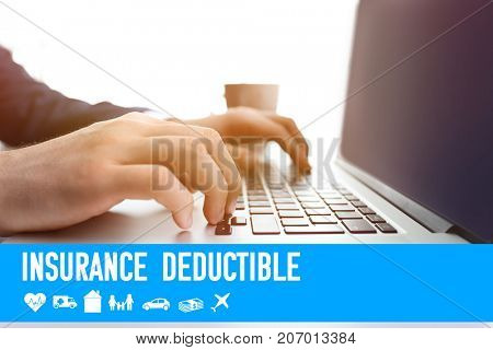 Man using laptop at table. Concept of insurance deductible