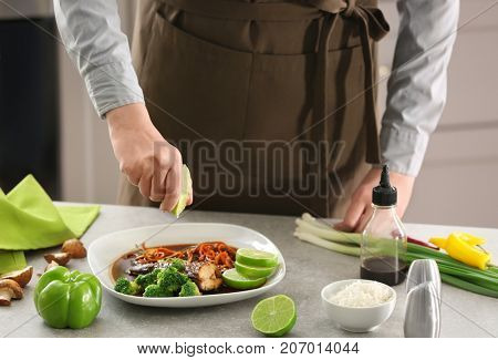 Chef squeezing lime juice onto plate with delicious fish in sauce and vegetables