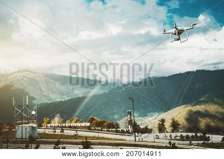 View of contemporary drone which is flying to capture on video of beautiful rainbow stretching between overgrown mountains in the background on sunny autumn day with small rain through sunshine