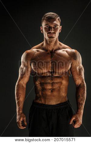 Very brawny guy bodybuilder posing. Beautiful sporty guy male power. Fitness muscled man in studio. Dark background.