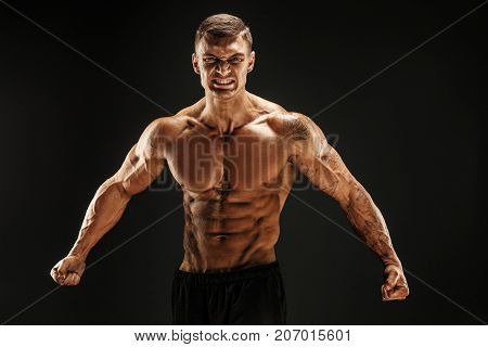 Very brawny guy bodybuilder posing. Beautiful sporty guy male power. Fitness muscled man. Roar