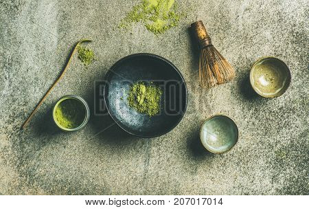 Flat-lay of Japanese tools for brewing matcha tea. Matcha powder in tin can, Chashaku spoon, Chasen bamboo whisk, Chawan bowl and cups over concrete background, top view, horizontal composition